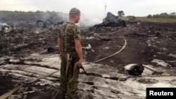 Боевик перед обломками «Боинга». 17 июля 2014 года
