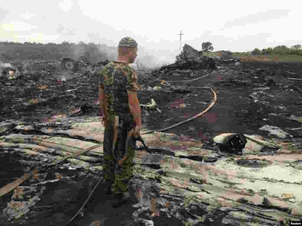 "A pro-Russian separatist fighter stands at a site of the Malaysia Airlines plane crash in the settlement of Grabovo in the Donetsk region. Shortly before the crash, a separatist leader boasted on social media that his men had shot down an aircraft. Later, the self-styled prime minister of the self-declared ""Donetsk People's Republic,"" Aleksandr Borodai, claimed the Ukrainian air force shot down the plane."
