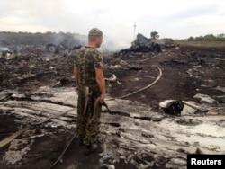 Пророссийский боевик-сепаратист стоит на месте катастрофы самолета авиакомпании Malaysia Airlines. Донецкая область, 17 июля 2014 года.