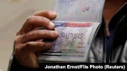 یک شهروند یمنی گذرنامه خود را نشان میدهد که اجازه ورود به آمریکا در روادید مربوط به ایالات متحده در آن لغو شده است.