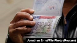 A member of the Al-Murisi family, Yemeni nationals who were denied entry into the United States because of a recent travel ban, shows the canceled visa in a passport from their failed attempt to enter the country. (file photo)