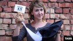Jurnalista Iulia Daraşkevici pozează cu un ursuleț de în fața unui tribunal de la Minsk în semn de solidaritate cu fotograful Anton Suriapin, care a fost arestat.