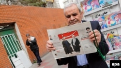 An Iranian man holds a copy of the daily Sharq newspaper with pictures of Iranian President Hassan Rohani and headline reading 'Decisive victory for the reformist' outside a kiosk in Tehran. Undated