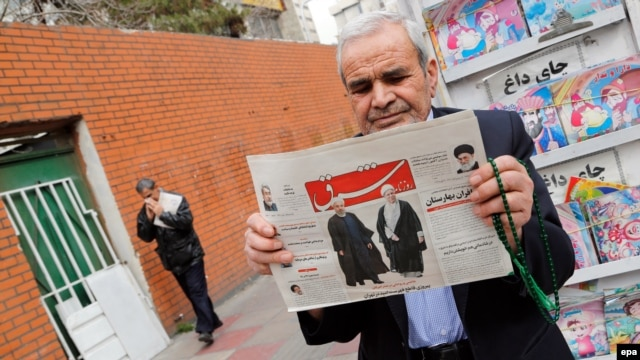 A man in Tehran holds a copy of the daily newspaper Shargh with pictures of Iranian President Hassan Rohani and former President Akbar Hashemi Rafsanjani and a headline reading: Decisive Victory For The Reformists.