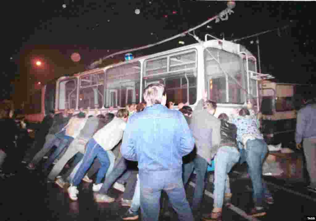 1991 жылы тамыздың 21-іне қараған түні Мәсекудегі Садовое кольцо мен Новый Арбат қиылысында әскерилердің жолын бөгеу үшін баррикада орнатып жатқан адамдар.