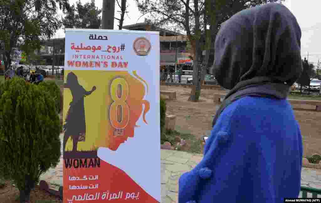 زن عراقی در حال خواندن پوستری بهمناسبت روز زن در موصل
