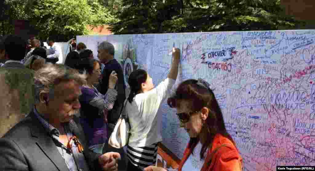 Люди пишут на специальной стене слова благодарности ветеранам Второй мировой войны. Алматы, 9 мая 2013 года.