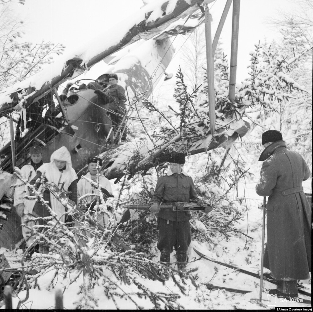 A downed Soviet plane being picked apart by a Finnish patrol.