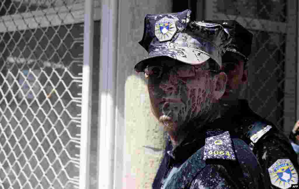 A policeman is covered in paint during clashes with demonstrators in Pristina who were against the ratification of an agreement with Serbia. Protesters from a radical nationalist movement attempted to block the entrance to Kosovo's parliament to prevent deputies from ratifying an agreement that would normalize ties with Serbia. (AFP/Armend Nimani)