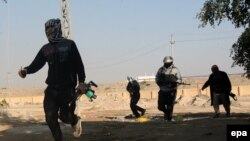 Masked Sunni gunmen take up position during fighting in Fallujah, iraq. (file photo)