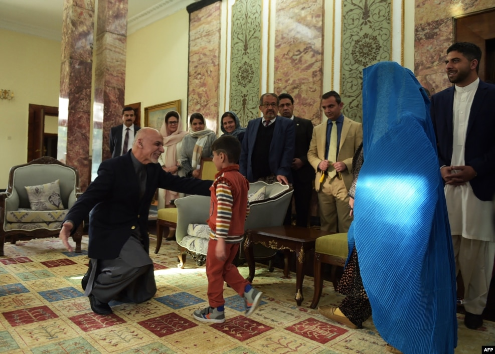 Afghan President Ashraf Ghani (left) greets the son (center) of refugee Sharbat Gula (second right) at the Presidential Palace in Kabul following her deportation from Pakistan on November 9. (AFP/Shah Marai)