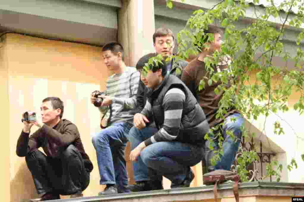 Оппозицияның жиналысын дуалдың үстінен бақылап тұрғандар. Алматы, 1 мамыр 2010 жыл.