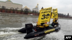 "Greenpeace activists hold flags reading ""Free the Arctic 30"" as they go past the Kremlin by boat."