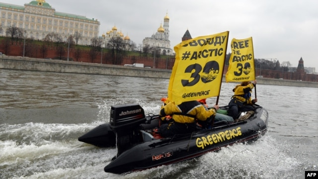 Greenpeace activists hold flags reading 'Free the Arctic 30' as they go past the Kremlin by boat.