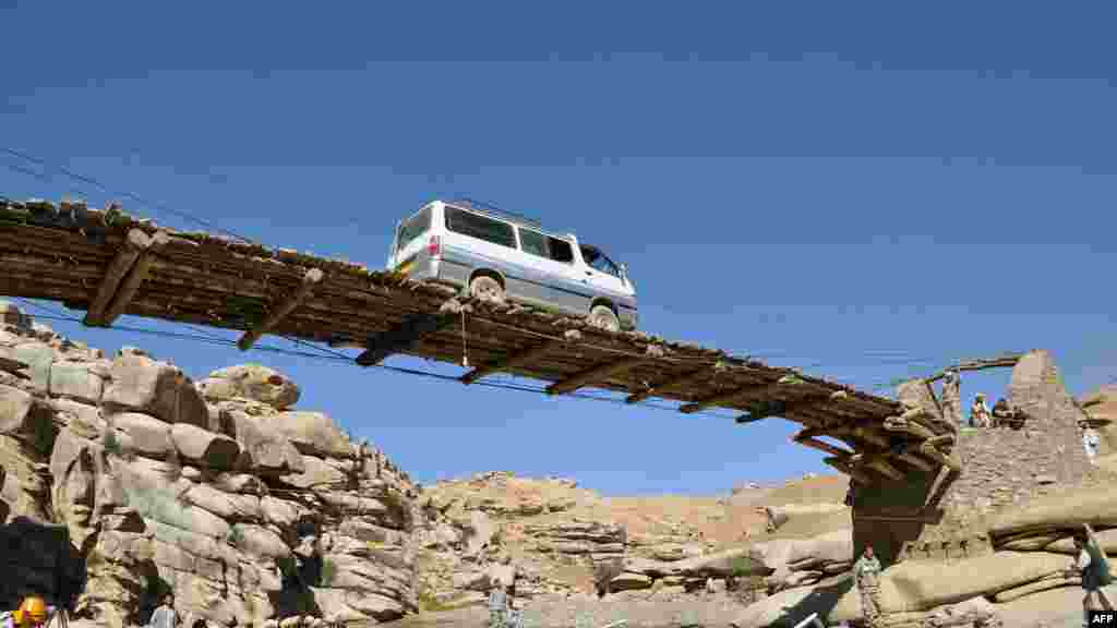 A vehicle drives over a wooden bridge in the province of Daykundi, Afghanistan. AFP PHOTO/Aref Yaqubi