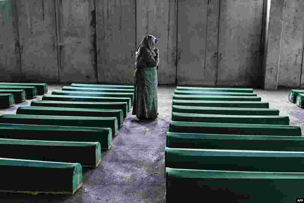 A Bosnian women mourns by the coffin of her relative in Srebrenica, where 136 bodies found in mass grave sites in eastern Bosnia will be reburied on the 20th anniversary of the Srebrenica massacre. Nearly 8,000 men and boys from the enclave were captured and systematically killed by Bosnian Serb forces in the days after the fall of Srebrenica on July 11, 1995. (AFP/Dimitar Dilkoff)