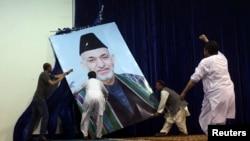 Сайлаушылар бұрынғы ауған президенті Хамид Карзайдың портретін сахнадан түсіріп жатыр.