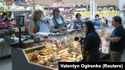Customers shop for meat products at the Bessarabsky market in central Kyiv.