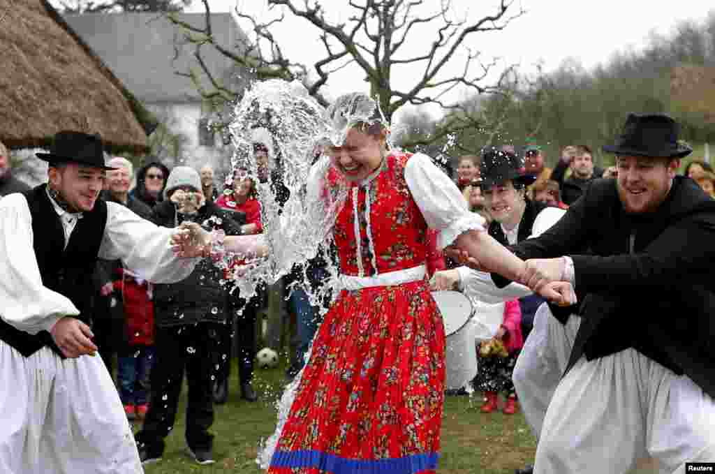 Men throw water on a woman as part of traditional Easter celebrations in Szenna, Hungary. (Reuters/Laszlo Balogh)