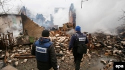 OSCE observers inspect a building that was destroyed after reported shelling in Avdiyivka in eastern Ukraine in February.