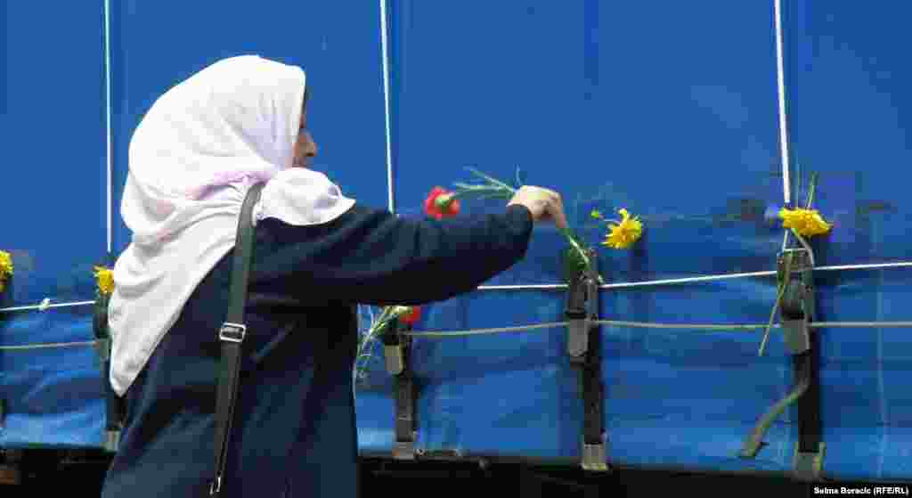 A woman puts a flower on a truck carrying the remains of people killed in Srebrenica in 1995 as it drives through Sarajevo.