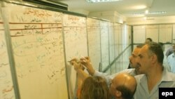 Stockbrokers write prices on a board at the Iraqi Stock Exchange