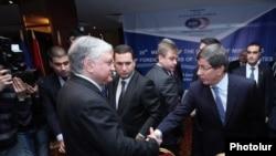 Հայաստանի և Թուրքիայի արտգործնախարարները ողջունում են միմյանց «Արմենիա Մարիոթ» հյուրանոցում: 12-ը դեկտեմբերի, 2013թ.