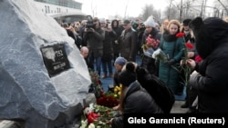 People lay flowers during a foundation stone laying ceremony for a future memorial site to the people killed in a plane shot down in Iran in January, at the Boryspil International Airport outside Kyiv, February, 17, 2020
