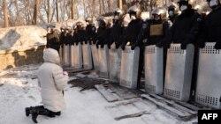 Жінка стоїть на колінах перед правоохоронцями на Грушевського, Київ, 24 січня 2014 року