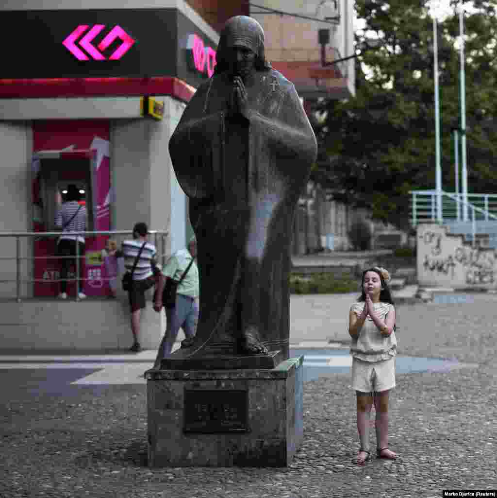 A girl imitates the Mother Teresa monument in central Skopje. Born to ethnic Albanians under Ottoman rule, Anjezë Gonxhe Bojaxhiu dedicated her life to the poor and sick of Calcutta and was beatified in 2016.