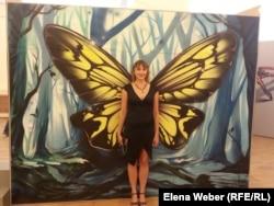 Девушка фотографируется на фоне картины с изображением бабочки. Караганда, 6 августа 2014 года.