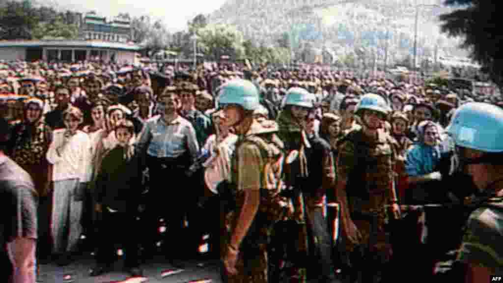 გაეროს ჰოლანდიელი ჯარისკაცები დგანან ბოსნიელ მუსლიმ ლტოლვილებთან პოტოკარიში, 1995 წლის ხოცვა-ჟლეტამდე. პოტოკარიში მდებარეობდა გაეროს ჰოლანდიური ბაზა სრებრენიცის ანკლავში.