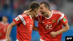 Russian midfielder Roman Zobnin (left) and forward Artem Dzyuba celebrate the team's opening goal against Egypt in St. Petersburg on June 19.