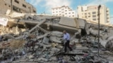 Palestinalylar 5-nji maýda Gazada ýumrulan jaýy barlaýarlar.