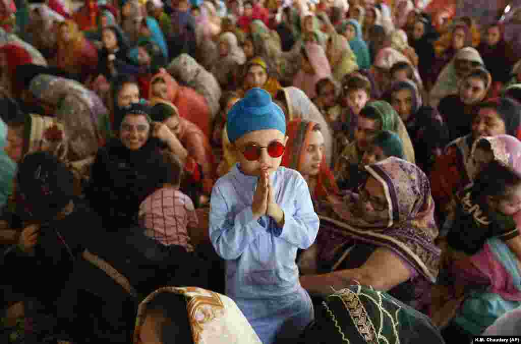 A Sikh child stands beside his mother attending a ceremony to observe the Martyrdom Day of a celebrated guru in Lahore on June 16.