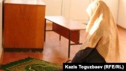 Намаз оқып отырған әйел. Алматы, 2010 жыл. (Көрнекі сурет).