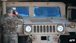 Украінскі вайсковец здымае прэзыдэнта Пятра Парашэнку, які сядзіць у браняваным аўтамабілі. Падчас цырымоніі сустрэчы першага амэрыканскага самалёта зь нелетальнай дапамогай. Кіеў, 25 сакавіка 2015