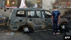 A boy inspects a burn-out vehicle the day after a bomb attack near a funeral tent in the Sadr City district of Baghdad, which killed several people on September 21. There have been three deadly attacks on funerals in as many days in Iraq.