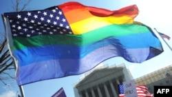 Сторонники однополых браков размахивают флагом ЛГБТ-сообщества перед зданием Верховного суда в Вашингтоне.