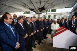 Binali Yıldırım török miniszterelnök és Ahmet Davutoğlu volt török miniszterelnök áll a legendás háromszoros olimpiai aranyérmes török súlyemelő, Naim Süleymanoğlu koporsója mellett Isztambulban, a 2017. november 19-én tartott gyászszertartáson