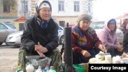 Хлебодар ауылының тұрғыны Қамажай Тәжімбетова (ортада) жайма базарда сүт өнімдерін сатып отыр. Ақтөбе қаласы, 13 қазан 2013 жыл.