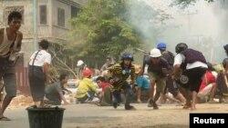 На кадре из видео, полученном агентством Reuters, протестующие укрываются во время столкновений с силами безопасности в мьянманском городе Монива, 21 марта 2021 года.