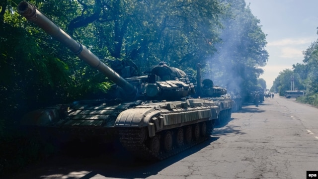 A column of pro-Russian militants with two Russian T-64 tanks and several APCs stand outside of Horlivka in Ukraine's Donetsk region on June 20.