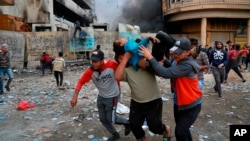 A wounded protester is carried away during clashes with security forces in Baghdad on November 28.
