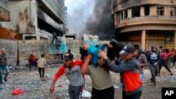 Протестующие несут раненного во время столкновений с силами безопасности. Багдад, 28 ноября 2019 года.
