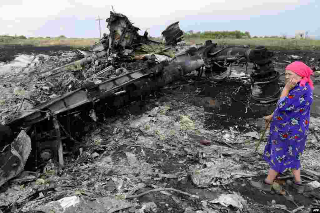 A local resident stands amid the wreckage at one of the crash sites near Hrabove on July 19.