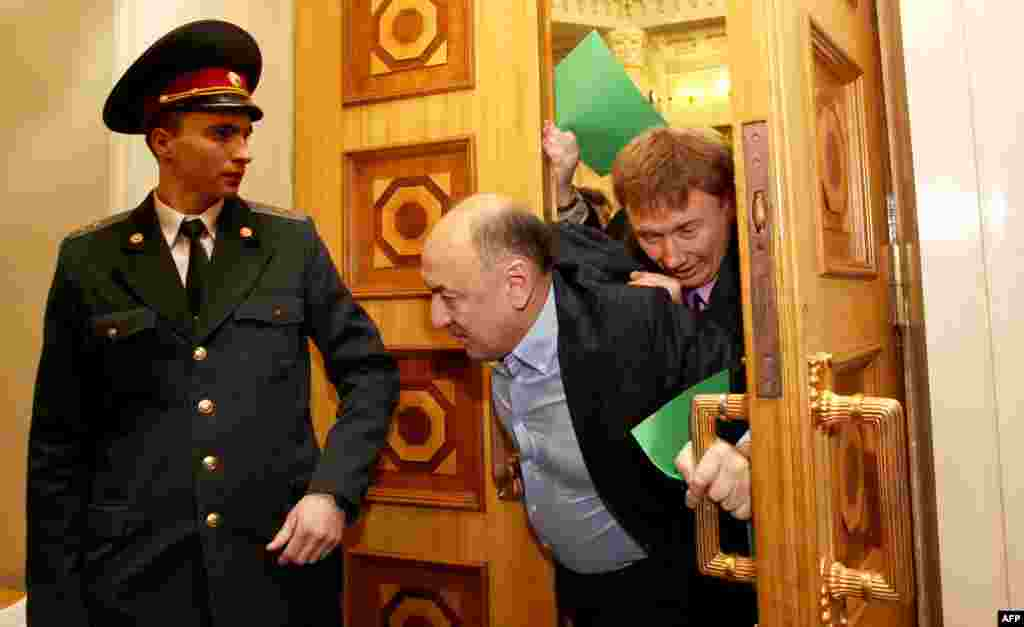 A policeman steps aside as father and son Andriy and Oleksandr Tabalov are driven out of Kyiv's parliament chamber under a hail of fists and insults. The pair were accused of preparing to switch sides and join the ruling party in December 2012.