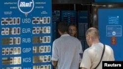 Мужчины у пункта обмена валют в день, когда правительство объявило о переходе к «свободно плавающему обменному курсу» тенге. Алматы, 20 августа 2015 года.