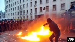 Unul din protestatari aruncînd cu pietre în polițiști în cursul tentativei de atac asupra Biroului Prezidențial de la Kiev
