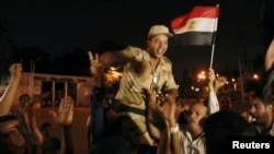 A soldier cheers with protesters opposed to Egyptian President Muhammad Morsi as they celebrate in front of the Republican Guard headquarters in Cairo after Morsi was deposed late on July 3.